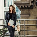 Lauren Cregan stands on balcony in Denver with ballet shoes and laptop