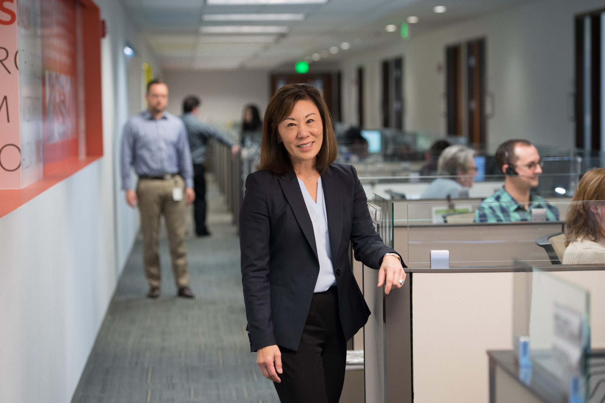 Becky Takeda-Tinker stands in office setting