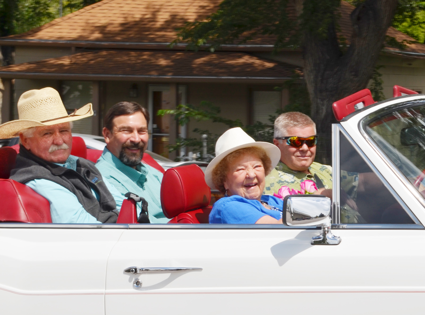 Betty Hood, Tony Frank, Terry Gale and Mark Trostel ride in the Grand Marshal's car