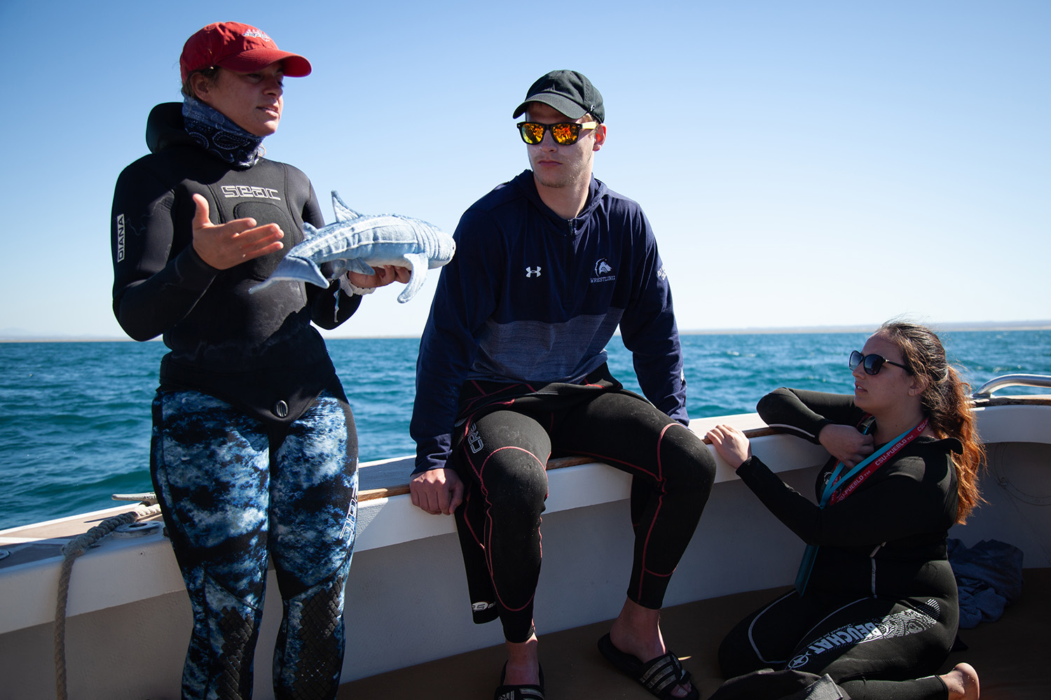 Dive instructor Crissy Cappellano describes the whale shark to A.J. Cross and Lilyana Lahti