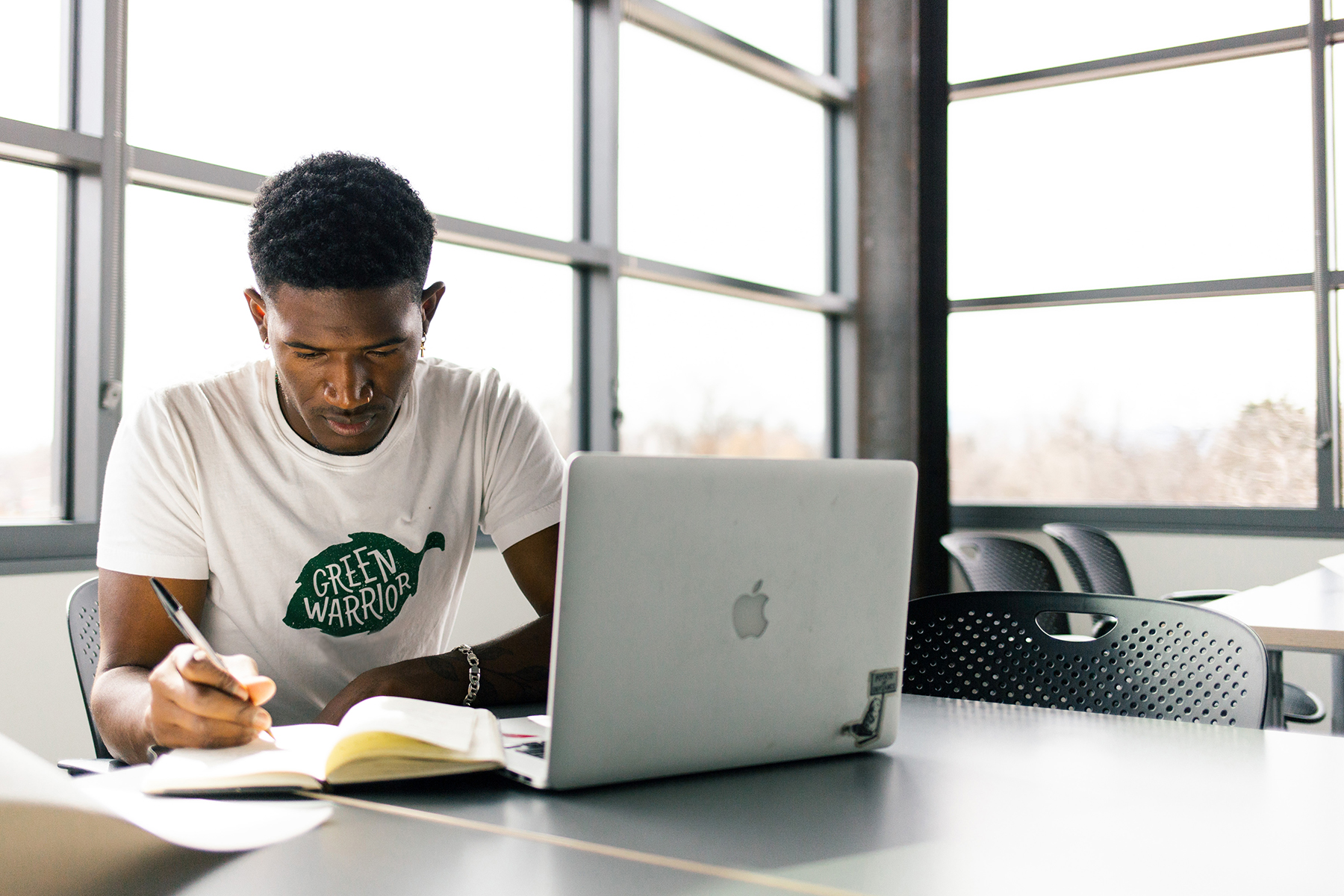 student studying with laptop and windows in background